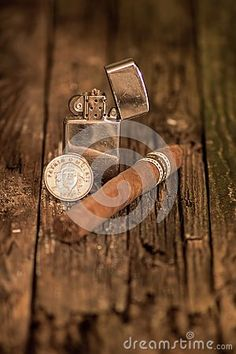 Photo about Still life photo of a cuban cigar, real cuban coin featuring Ernesto `Che` Guevara on the back and a lighter on aged vintage wood. Image of dark, vintage, cuban - 129496662 Ernesto Che, Cuban Cigars, Still Life Photos, Vintage Wood, Be Still, Lighter, Che Guevara, Coins, Wedding Rings