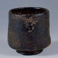 写真:黒樂筒茶碗 惺斎追銘「老松」 樂長次郎作 桃山時代 16世紀 なだらかに下へ伸びた線から低く張り出した腰が安定感を与え、その底を大振りの高台ががっしりと受け止めている。 やや不整形な趣きながら、ずっしりとした存在感がある筒茶碗。高台ごと掛けられた黒釉は全体にカセており、正面に降り掛かった灰が鱗形の景色となる侘びた風情。 樂家初代長次郎(?~1589)の、最晩年の境地を示す作と見られる。