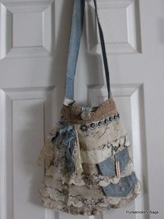 Large handbag made with thick, soft beige and floral fabrics. Ruffles throughout the front body with vintage doilies, lace and denim and a