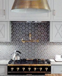 Black and gold range, gold pendant lighting and gold plumbing fixtures is a great contrast to the backsplah