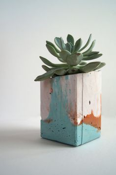 A square, concrete vessel/planter with interesting layers and marked surface. Made up with very light pink, muted turquoise and copper, rusty tones. £25 This item is carefully hand made from start to finish by Emma McDowall - an artist & maker based in Scotland. Each piece is completely unique in design, and moulded from recycled materials. Size: height 10cm x 7cm x 7cm x depth 7cm