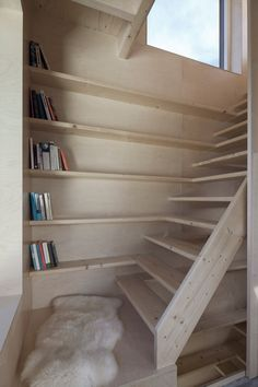 Book shelves run up the back wall of the stairway, adding storage space and providing a point of visual interest in the stairwell.