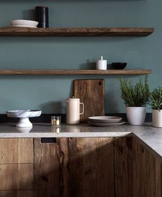 Mid-tone natural wood cabinets, floating shelves, dark blue-green paint color | modern rustic kitchen