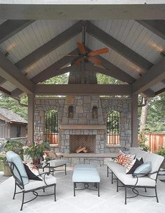 The pavillion is an elevated covered terrace with a stacked stone fireplace and flagstone floors. Gas Sconces, beaded board ceiling, cedar timbers and custom iron winodw grills define  the space. Photography: John Umberger; Real Images