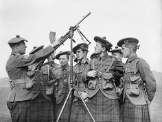 Soldiers of the 1st Battalion Cameron Highlanders receive instruction on a Bren gun fitted on an anti-aircraft mounting at Aldershot, 1939.
