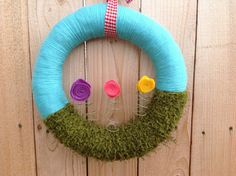 This adorable yarn wrapped wreath is perfect for spring or keep it up all summer long too! The wreath base is 14 inches and the top half is wrapped in sky blue yarn. The bottom half is wrapped in grass like fuzzy yarn. Three hand rolled felt flowers sit atop the flowers stems. It's a great piece for indoors or on your door. Makes a perfect housewarming gift.