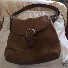 Coach bag  Pre-loved authentic Coach leather shoulder bag. Little stains on one side of the bag. The inside is immaculate. Light brown in color. Adjustable strap.  Coach Bags