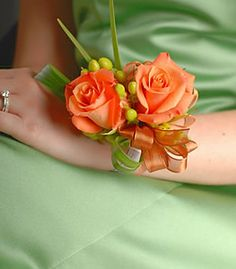wrist corsage of beautiful orange roses and hypericum