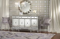 Round modern mirror with silver frame over mirrored sideboard