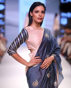Blush and navy blue sari with embroidered crescent motifs across length. This sari comes with a matching blush blouse with embroidered three quarter sleeves. Round neckline. Wash Care: Dry clean only.Disclaimer: There might be a slight color variation in this item as this image is from the actual runway show..