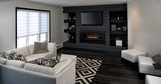 Living area with dark feature wall with wall-mounted T. and fireplace. Dark hardwood floors and light walls. Hardwood Floors, Dark Hardwood, Flooring, Living Area, Living Room, Wall Mounted Tv, Fireplace Design, Light Walls, Wall Lights