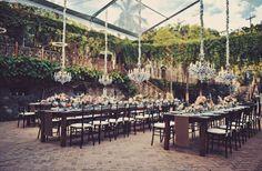 Vintage chandeliers and dark wood tables set an elegant dinner