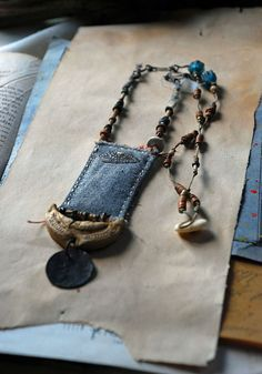 Love the gypsy, mystical and rustic feel of this handmade necklace! Clay charm w/ ottoman coin hanging from it & above is a vintage cloth rectangle sewn around a paper from an old personal note she found (for stability & memory)- handmade rust Evil Eye sewn on it...