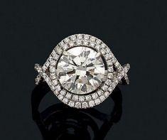 Bague en or gris 18k sertie d'un diamant de taille moderne dans un double entourage de petits diamants.  Tour de doigt: 54  Pb.: 4.9gr    Accompagné d'un certificat HRD précisant  Poids du diamant central:… - Aguttes - 31/03/2016