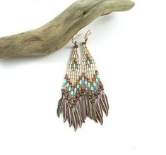 Beadwoven earrings with fringes, made of Japanese Toho nad Miyuki seed beads, bugle beads and copper feathers. Colors: gold lined crystal, turquoise, brown Length - 8,8 сm / 3,5 inches (including ear wires) Width - 1 -1,5 cm (at the bottom) / 0,4- 0,6 inch (at the bottom) Earrings are not heavy. They are very comfortable while wearing. Gift box included ************************************************************************************ ***Please note that due to lighting effe...