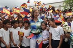 Spain's Queen Sofia is surrounded by school children upon her arrival at the Camalig Evacuation Center for Natural Disasters, which is funded by a Spanish government agency, during her visit to Legaspi city, south of Manila July 4, 2012.