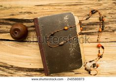 Book on table with necklace and candle - stock photo