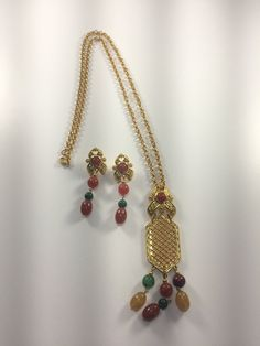 Presenting a lovely bohemian chic mod demi parure. This necklace and earrings feature gold tone metal and semiprecious stones that dangle. Very