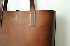 Hand-Stitched with good quality Italian vegetable tanned cow leather, it will age to very great color after you used it - Stylish and special - suitable volume for daily use - can include A4 size document - Approx. dimension 30cm(W) X 30cm(H) X 9cm(D). - Handle drop 11cm - Dark brown, Black, Beige color leather are also available now!  * Larger version: https://www.etsy.com/hk-en/listing/197235856/hand-stitched-light-brown-leather-tote?  For the leather color example, please go to below…