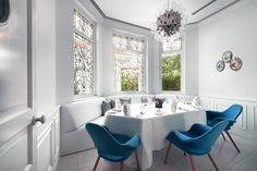 This dining table is tucked into bay windows with banquette seating as well as a few chairs.