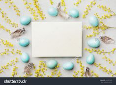 Painted Easter eggs, mimosa flower and paper card on vintage stone background top view in flat lay style. Empty space for text.