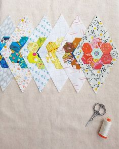 A nice way to use hexigon flowers in a quilt. I would applique them on my background fabric.
