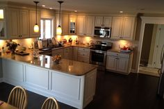 U shaped kitchen design with American Woodmark cabinets; Savannah Maple white with hazelnut glaze. Granite countertop and stainless steel appliances.