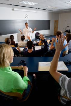 Stock Photo : Students raising hands in the classroom