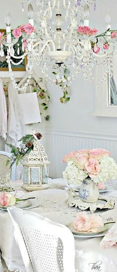 Shabby Chic Style Dining Room with Crystal Chandelier and Fresh Flowers Arrangements.