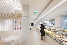 ilia estudio interiorismo: Tiras de madera blanca con forma orgánica para esta pastelería de Oporto