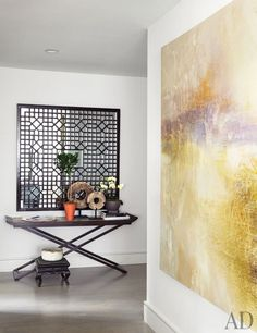 The foyer and adjacent hall display a painting by British artist Daisy Cook as well as a mirror-backed Chinese lattice window and Indonesian stone sculptures atop an X-base console, all from VW Home.