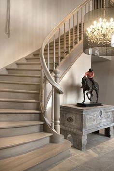 Mooie landelijke trap van grijs hout in dezelfde kleur als de tegelvloer. Mooie hanglamp als eyecatcher en stoere oude kast.