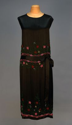SILK CHARMEUSE DRESS with IRIDILL BEADWORK, 1920's. Sleeveless black with slight gathers at sides below waist, having wide band of meandering floral beadwork at midriff and hem in rose pink, red, pale blue, emerald and white, self sash attached at side gathers. B-44, dropped W-40, L-45. Excellent. $510.