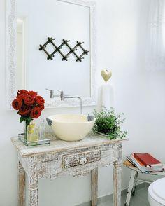 """O romantismo entra em cena em elementos como o papel de parede floral, a cuba de cerâmica feita à mão e o aparador e espelho de estilo provençal. """"Não se trata de um ambiente retrô"""", garante Leticia. """"A moradora queria uma casa com personalidade, um espaço cheio de referências da sua infância"""", explica.     Projeto: Leticia Muzetti; cuba: Ateliê Glória Queiroz; aparador e espelho: Adeusan."""