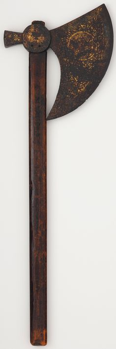 Syrian axe, 15th century, steel damascened with gold. Dimensions: Blade width, 9 1/4 in. (23.5 cm) Blade height, 10 1/4 in. (26.04 cm) Handle length, 27 in. (68.58 cm). Mamluk sultans and emirs employed a special corps of ax-bearers, probably in imitation of the Varangian (Viking) guard of the emperors of Byzantium. The cup decorating the socket of this ax is the insignia of a Mamluk emir and indicates that he held the important ceremonial office of cupbearer to the sultan. Metropolitan…