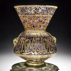 "Mosque lamp (Mamluk, Syria or Egypt, 14th century). ""This enamelled glass lamp was made for the madrasa of Sultan al-Malik al-Zahir Abu Sa'id Barquq. Around the neck is written part of Sura 24, Verse 35, of the Holy Qur'an"".  (Museum of Islamic Art in Qatar via http://www.mia.org.qa/en/visiting/mia-tours/year-of-light-3)"