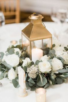gold lantern centerpiece surrounded by white garden roses and eucalyptus