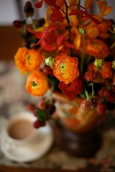 Ranunculus steals the show in the arrangement filled with all shades of orange for fall. Love the addition of fall raspberries. Bouquet of fall flowers in a vintage vase.