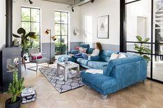 Conseil déco : une base neutre permet toutes les folies. La déco, les meubles, la peinture sur les murs déclinent ici des nuances de gris. Ainsi, vous pouvez oser les touches de couleur flashy et le canapé en bleu pétrole moiré format XXL.