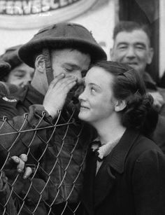 A young woman smiles as a soldier whispers to her over the fence before he ships off to the World War II front. September 24, 1939