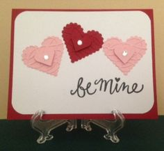 "Valentine's Day card with ""be mine"" greeting. Die cut scalloped and classic hearts from Spellbinders. Embossed with ProvoCraft Scrollwork. A rhinestone in the center of each."