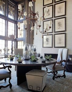 When you have vaulted or high ceilings, take advantage of the extra wall space and create an eye-catching display of artwork like this! There is a lovely balance between the windows and this art arrangement. NOTE: all the frames are the same and the so is the subject matter, this creates symmetry :) House Beautiful