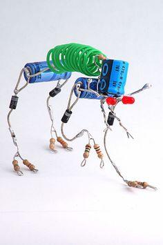 Escultura de robô feita a partir de capacitores, diodos, resistores, leds, pedaços de fio...