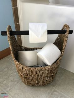 DIY toilet paper holder idea! Use a wicker basket with a wood handle as a toilet paper holder and fill the basket with extra toilet paper rolls. Works with tube free toilet paper rolls too!