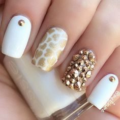 Creative looking white and gold nail art design with embellishments. The nails…