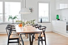 Black wishbone with wooden table and white kitchen