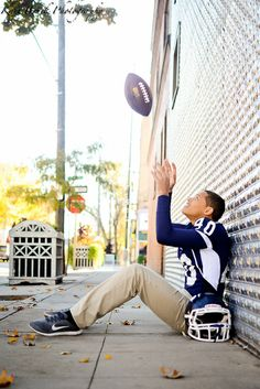 Kari Bruck Photography high school senior session pose idea for football players. High school senior boy inspiration for posing for football. Senior Pictures for a guy tossing a football in an urban setting. ports or Sport pictures.