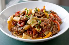Drunken Noodles, Italian style, with spicy Italian sausage, sweet and savory tomatoes, caramelized onions, red and yellow bell peppers, and fresh basil!