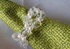 Conjunto de 04 anéis porta-guardanapos entrelaçado de acrílicos transparentes e pérolas brancas.  Trabalho feito artesanalmente, um a um. R$ 11,00