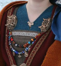 viking sca larp  the strings of beads and amulets like the thors hammer right in the middle attached to the two boss oval brooches.